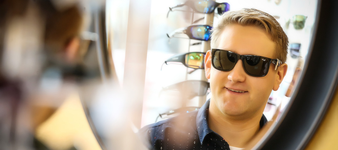 man trying on sunglasses and smiling